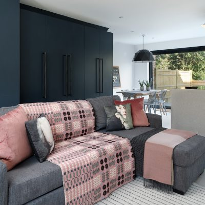 Open plan living room and kitchen with sofa, pink throws and cushions
