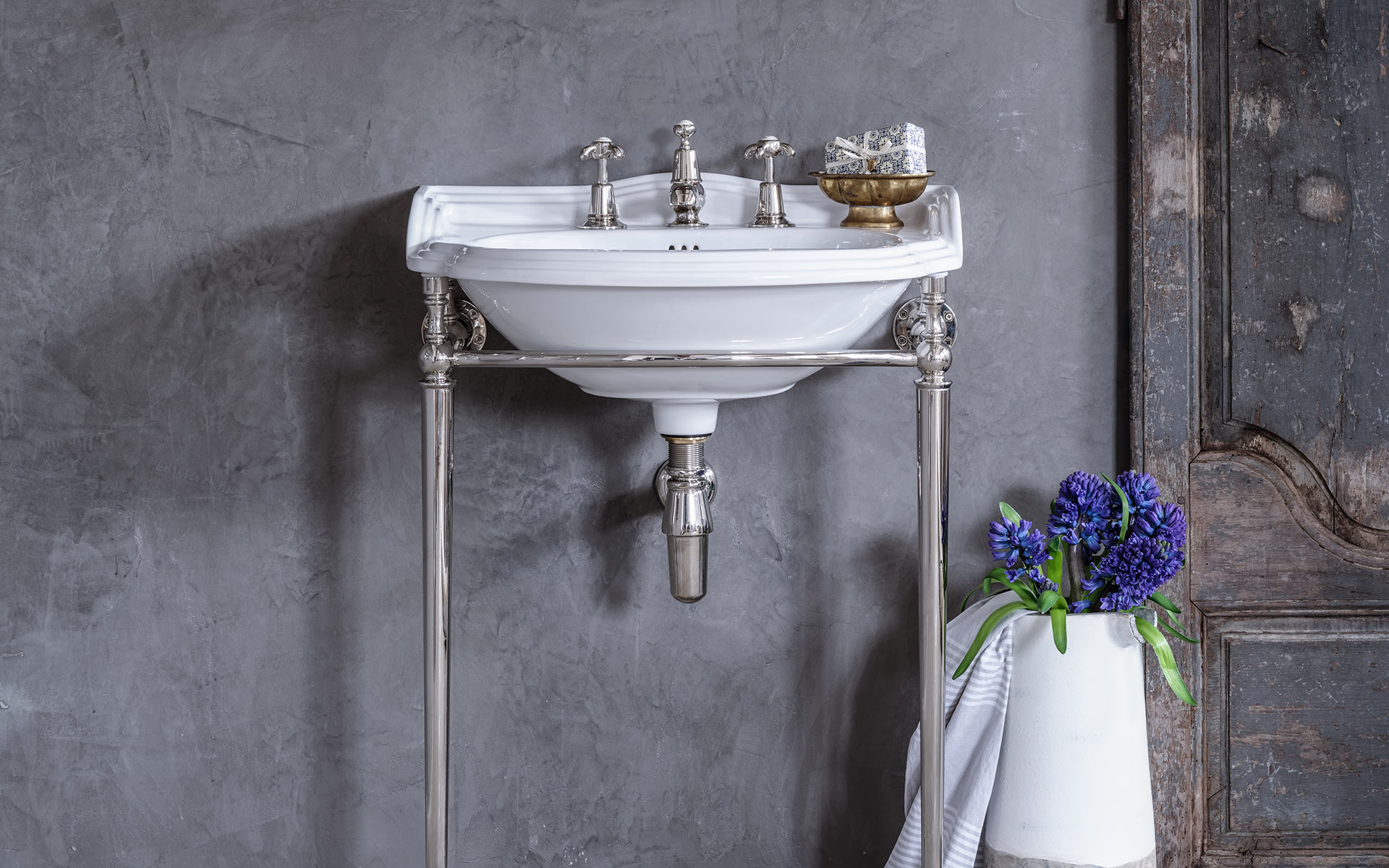 White luxury basin with fittings against polished plaster wall