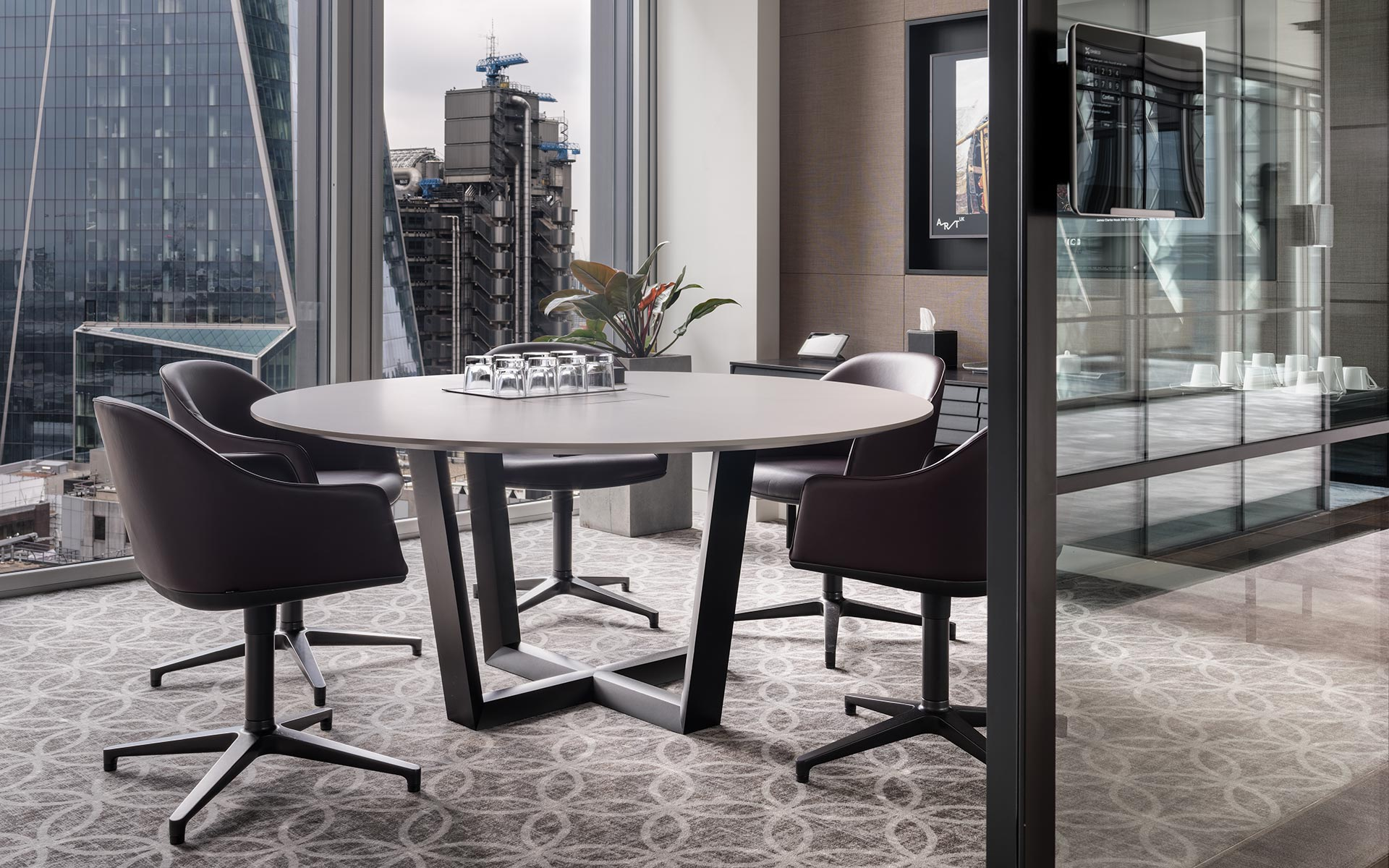 Bespoke round meeting table in small office with Lloyds of London Building in background